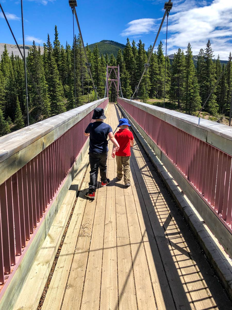 Kids crossing river bridge along Little Elbow hiking trail Kananaskis Alberta Canada
