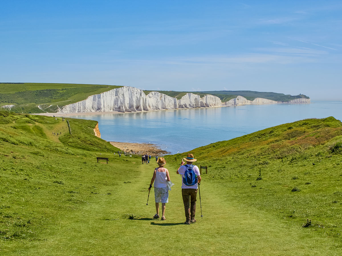 A couple walking towards the Seven Sisters Eastbourne South Downs UK