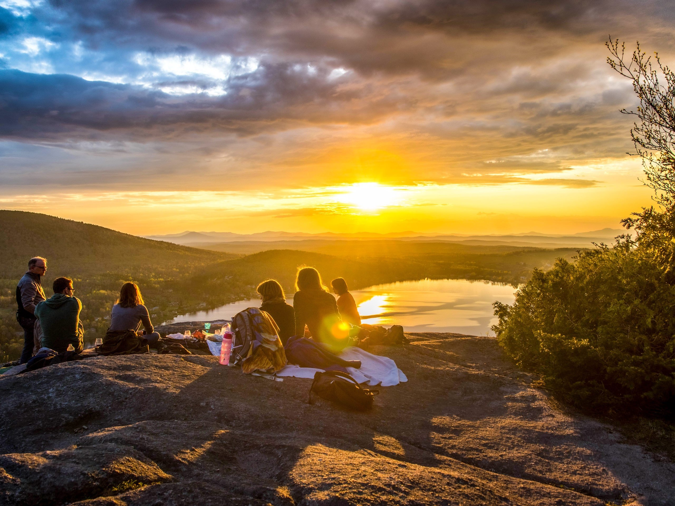 Friends hiking resting on rock lookout watching the sunset