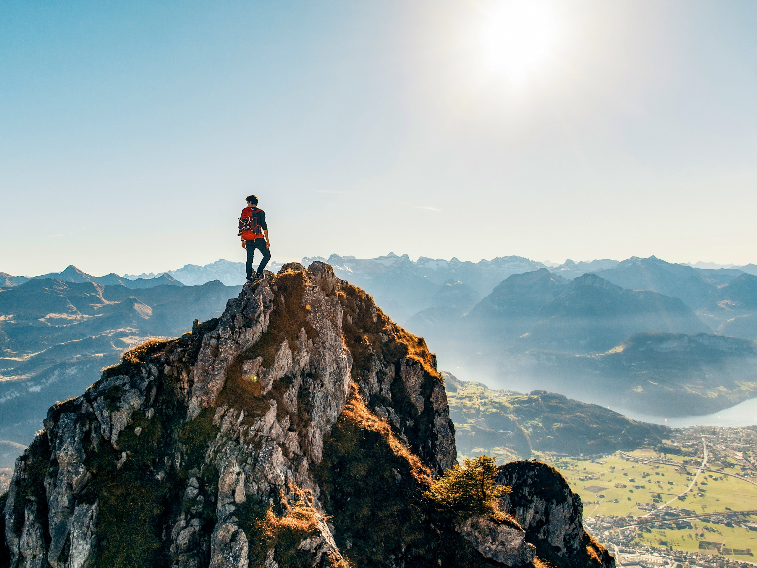 Hiker standing on top of tall rock peak looking out to mountains