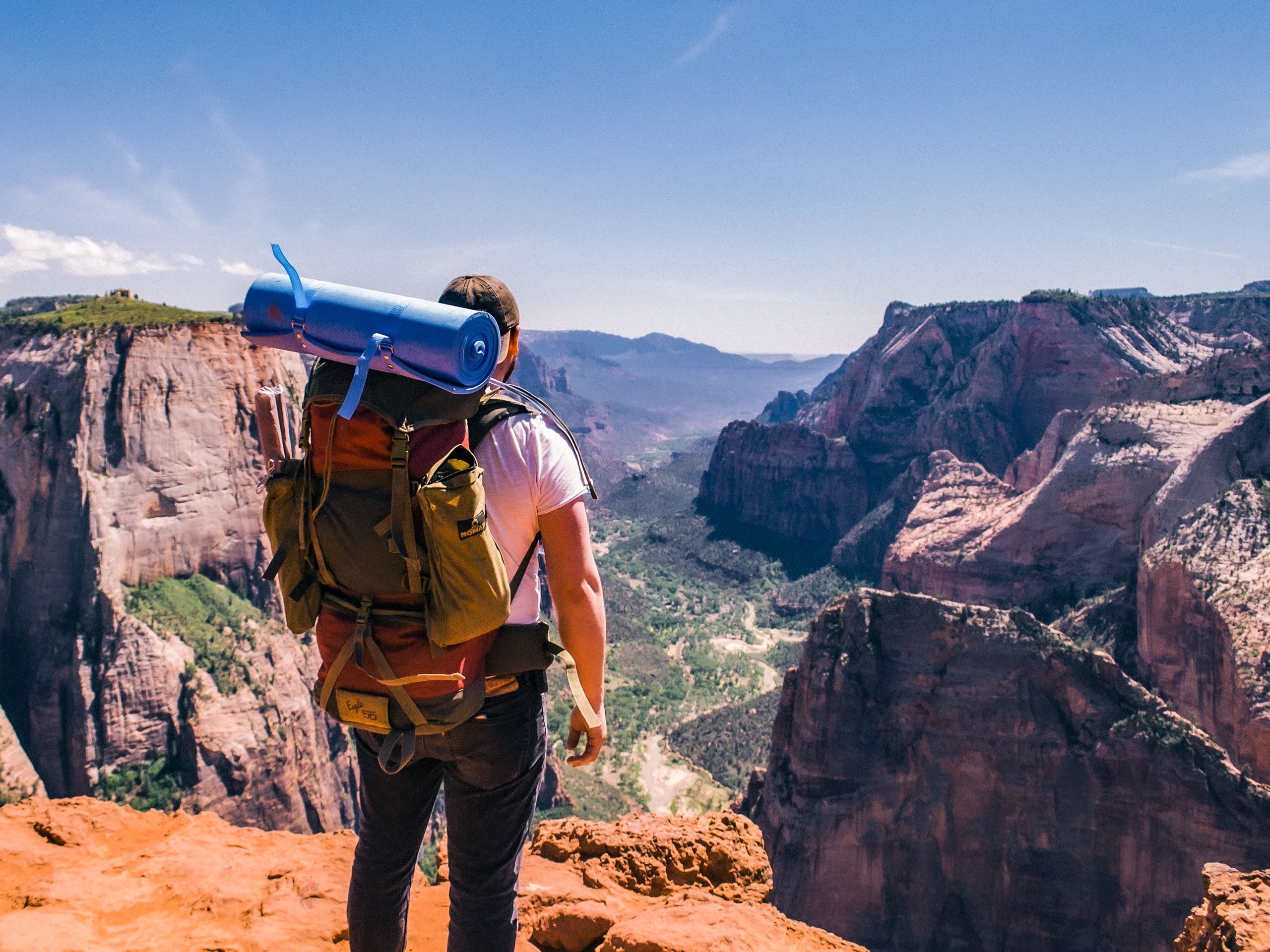 Man with backpack and camping gear standing above canyon