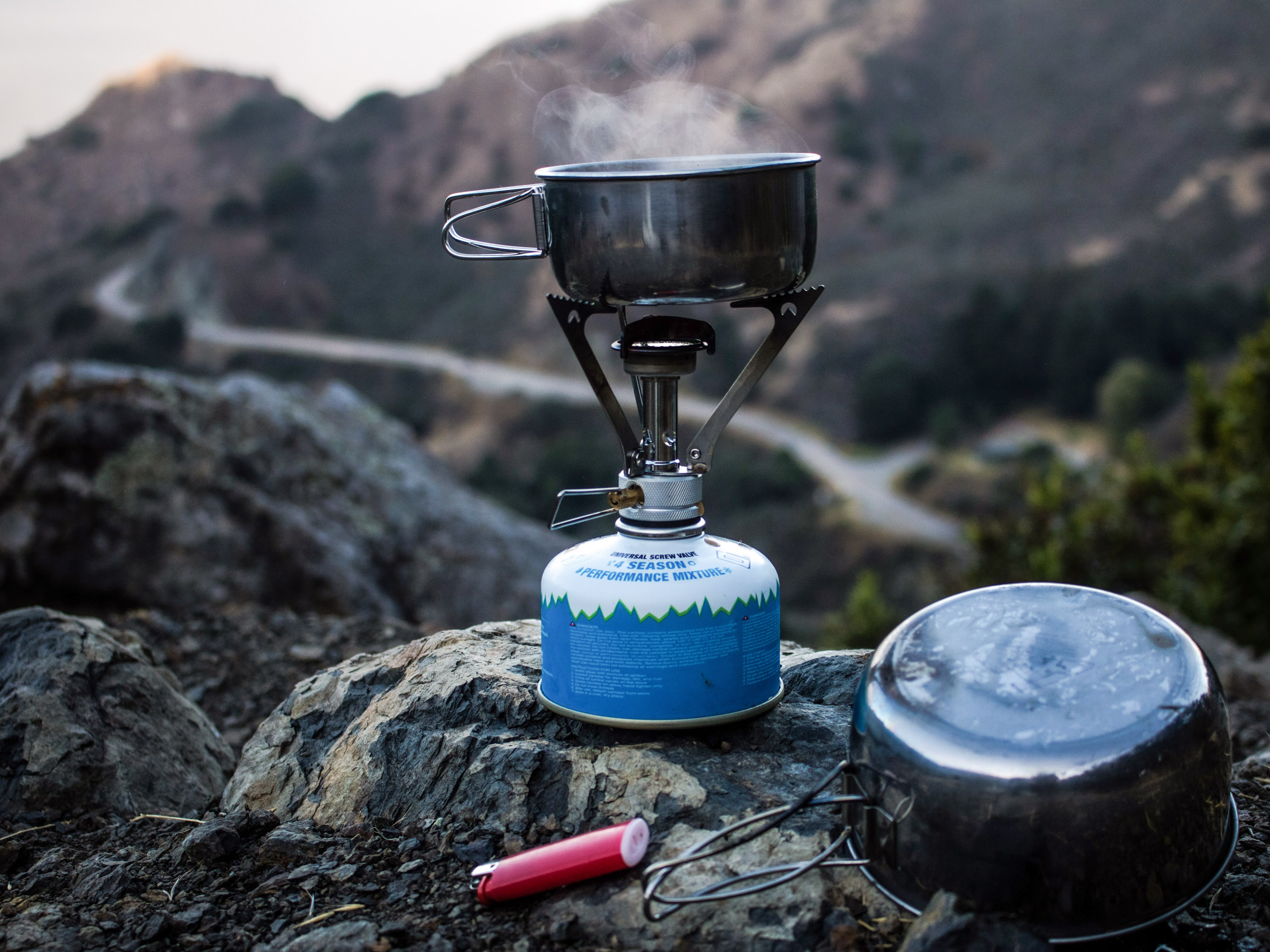 Steam rising from small pot on camp stove backcountry camp kitchen