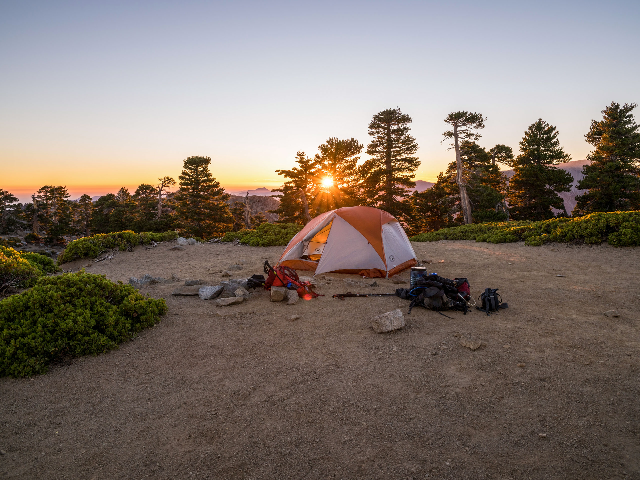 Sunrise sunset camping gear tent on mountain top lookout